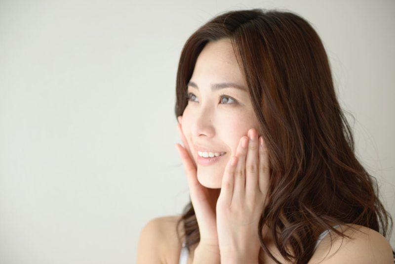 両頬に手を当てる日本人女性