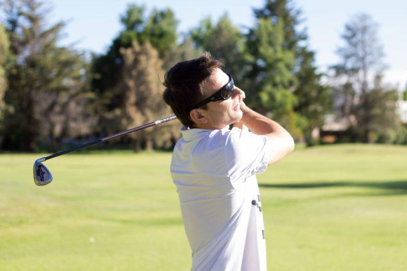 サングラスをかけてゴルフをする男性