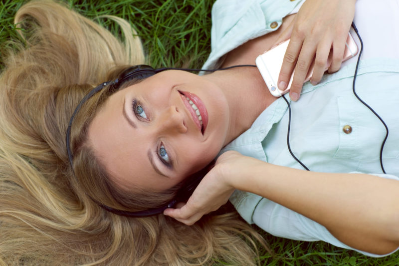 芝生に寝ころびながらスマートフォンで音楽を聞く外国人女性