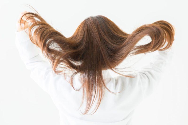 髪の毛を掻き上げる白い服を着た女性
