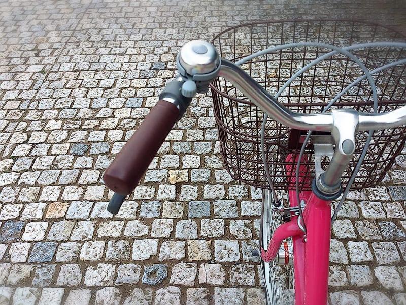 石畳の地面に自転車が停まってて前かごがズームされている