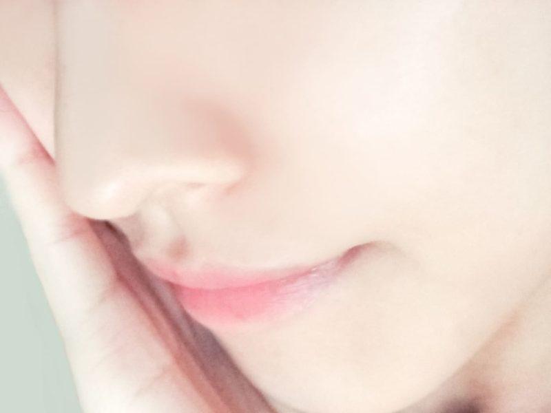 頬に手を当てる色白の女性