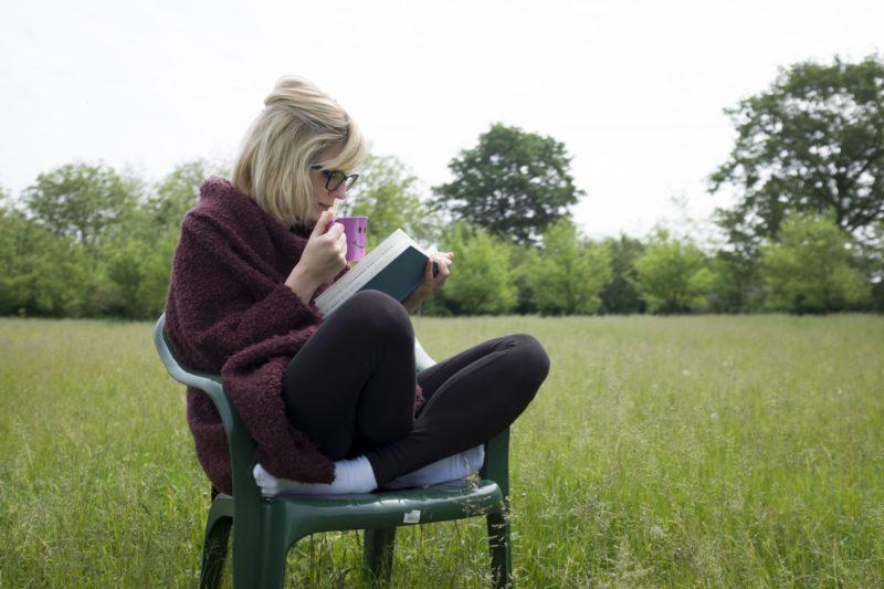 公園で椅子の上で読書する女性