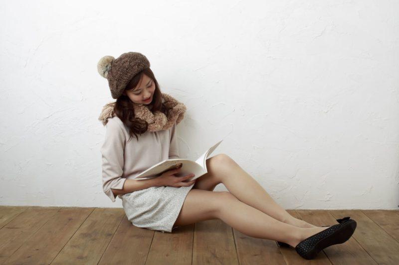 ボンボン付きのベレー帽を被った女性が本を読んでいる画像