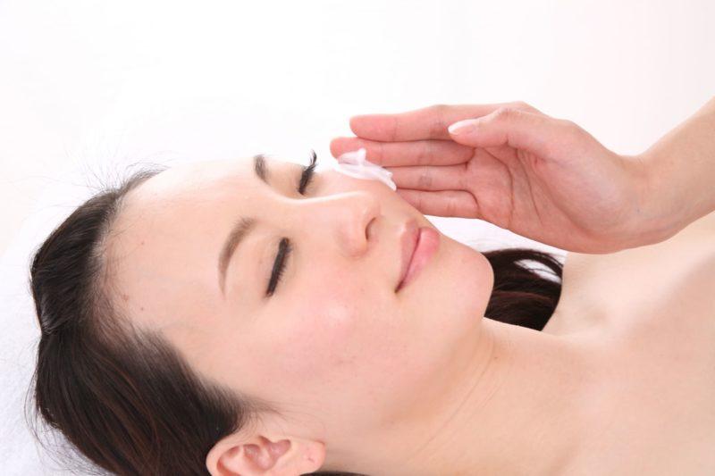美容クリームを肌に塗っている日本人女性