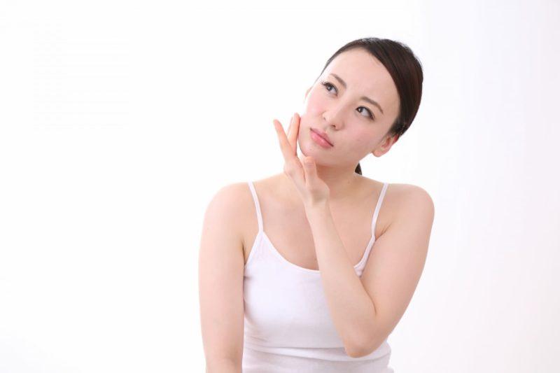 肌を触っている日本人女性
