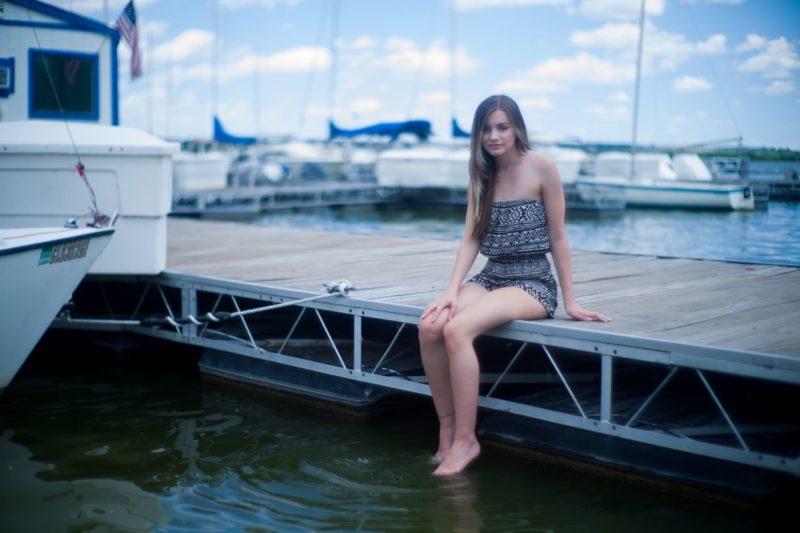桟橋で腰かけている外国人女性