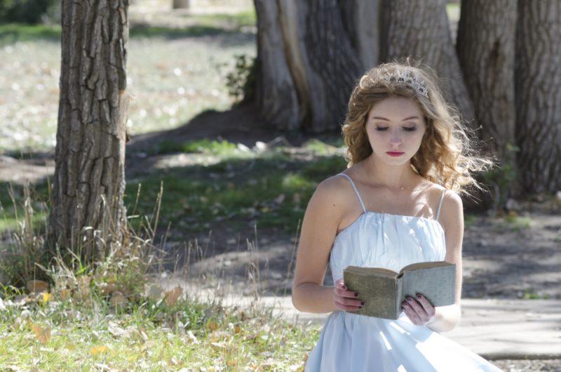 白いドレスを着て本を読んでいる外国人女性の画像