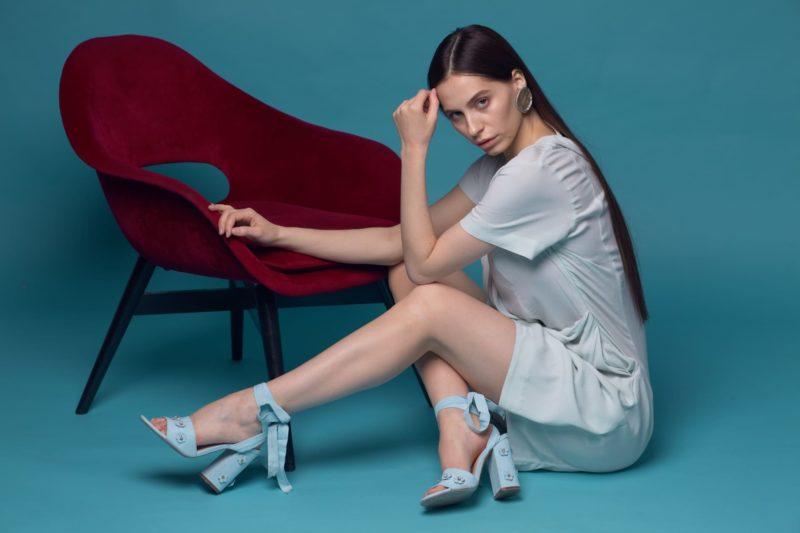 床に座り椅子に手をかけている白い服を着用した外国人女性