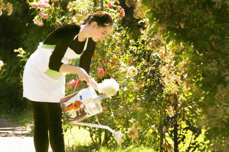草花に水を与えている花屋の外国人女性