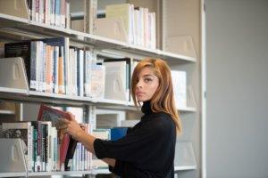 本棚の本に手をかけている茶髪で長髪の外国人女性