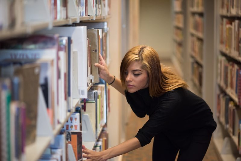 本棚に手を掛けている茶髪で長髪の外国人女性