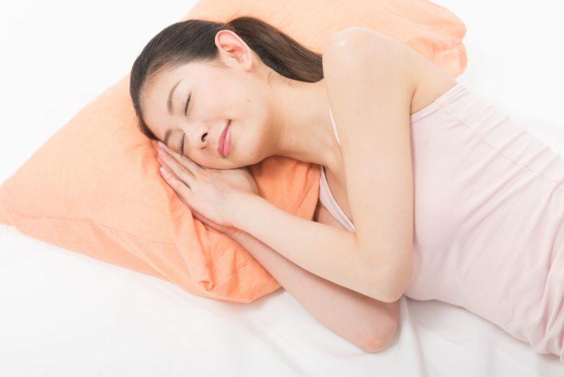 寝ているキャミソールを着用した女性