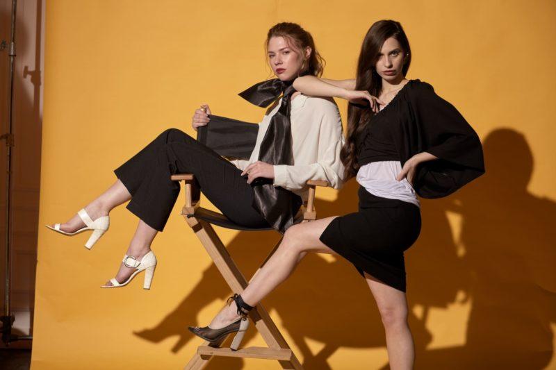 椅子に腰かける白い服を着用した女性と黒い服を着用した女性