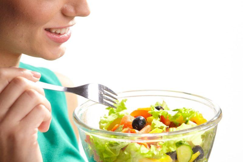 今、まさにサラダを食べようとしている女性