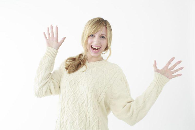 両手を広げて喜んでいる白いニット着ている女性