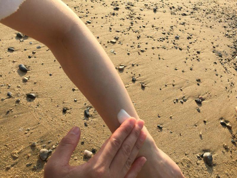 海岸の砂浜で日焼け止めを塗っている人の腕