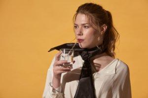 コップの水をストローで飲む白い服を着用した外国人女性