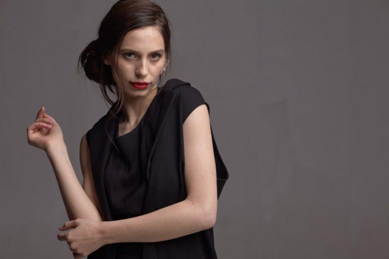ひじに手を当てている髪の毛を結んでいて黒い服を着用した外国人女性