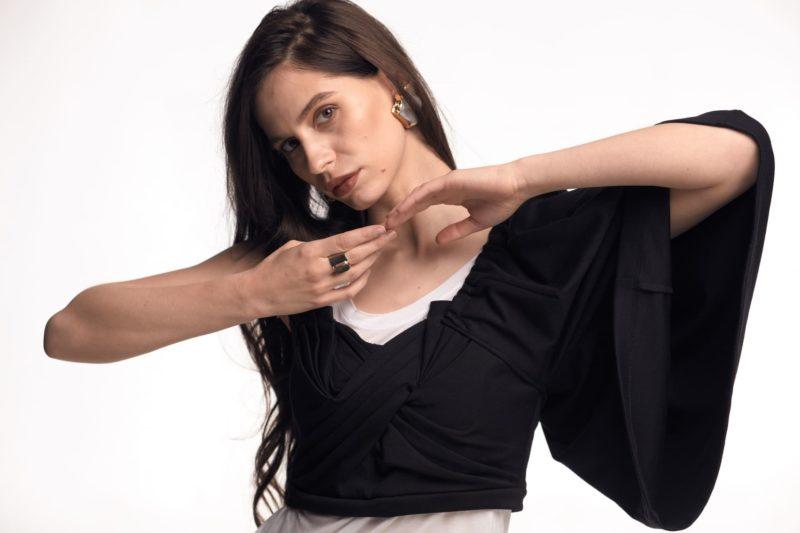 白い服と黒い服を着用している髪の毛を結んでいない長髪の外国人女性