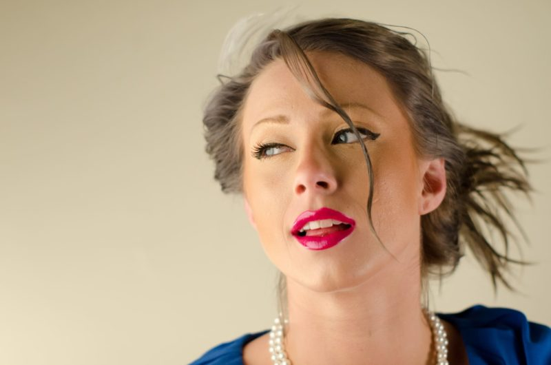 髪の毛を結んでいる青い服を着用した外国人女性
