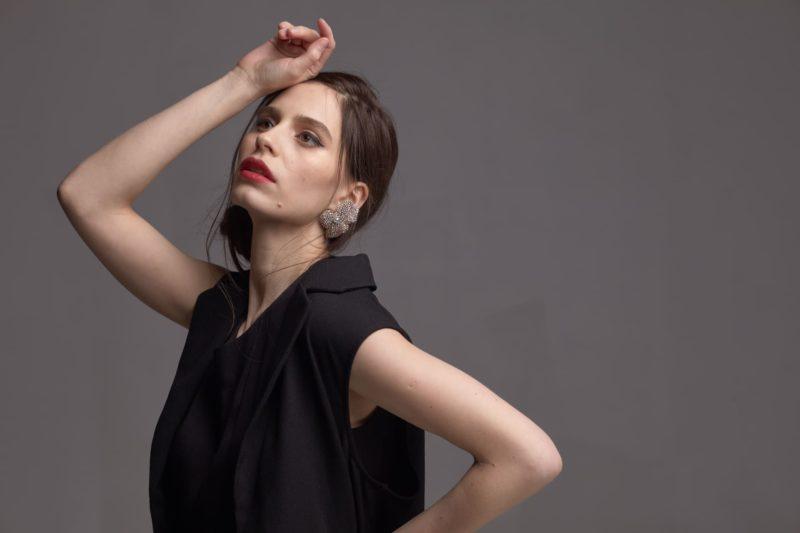 額に手を当てている黒い服を着用した外国人女性