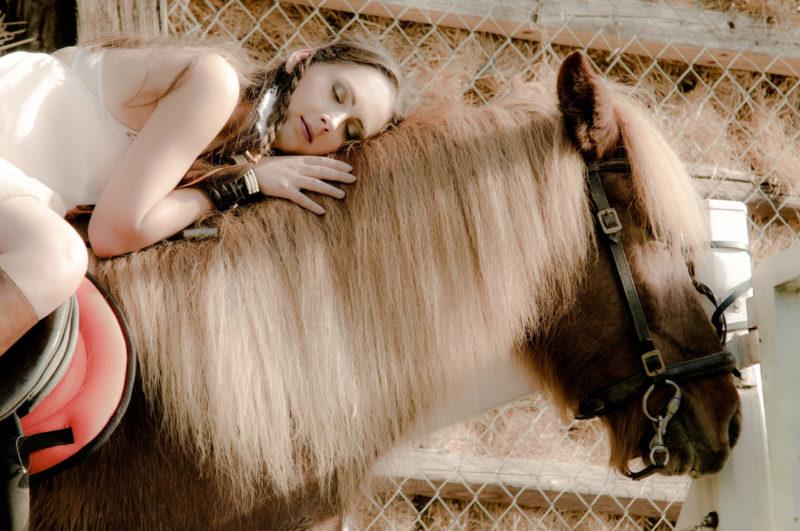 馬に乗り、寝そべっている外国人女性