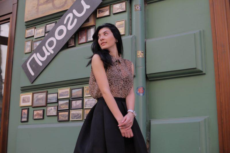 緑の写真や看板の前で佇む女性