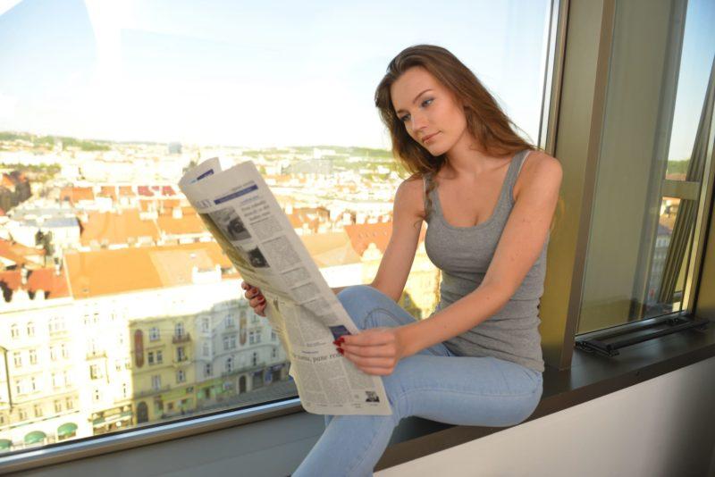 大きな窓際で新聞を読んでいる大人の女性