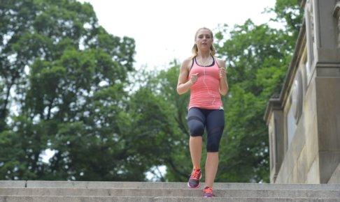木々がある階段をジョギングしている女性