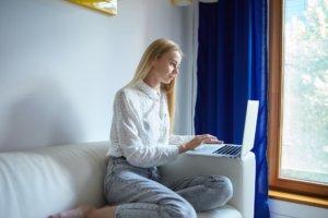 ソファーに座ってパソコンを入力している外国人女性