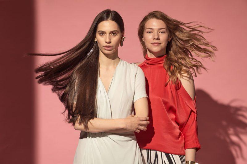 白い服を着用した外国人女性と赤い服を着用した外国人女性