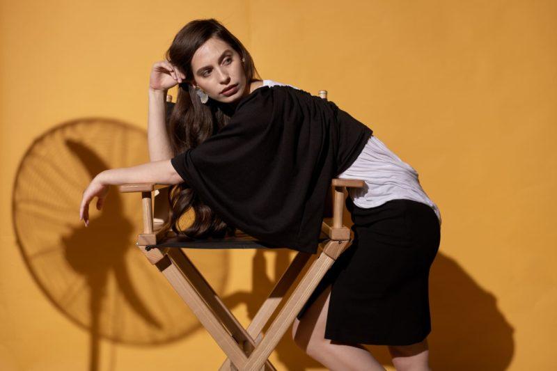 椅子に手を掛けている黒い服を着用した外国人女性