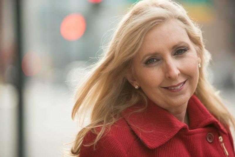 赤いコートを着ている年齢を重ねた外国人女性