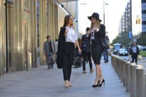 帽子を被っているスーツの女性と上着を脱いでいるスーツの女性