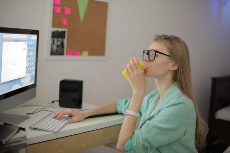 パソコンを操作しながら飲み物を飲んでいる外国人女性