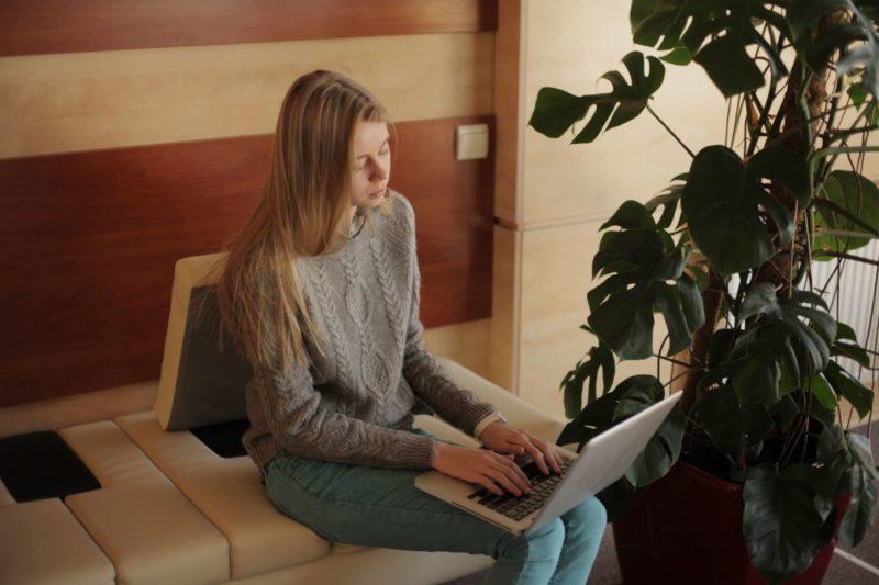 ソファーに座ってパソコンを操作している外国人女性