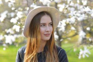 花を背に立っている帽子を被った外国人女性