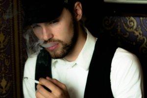 煙草を吸っている帽子を被った外国人男性