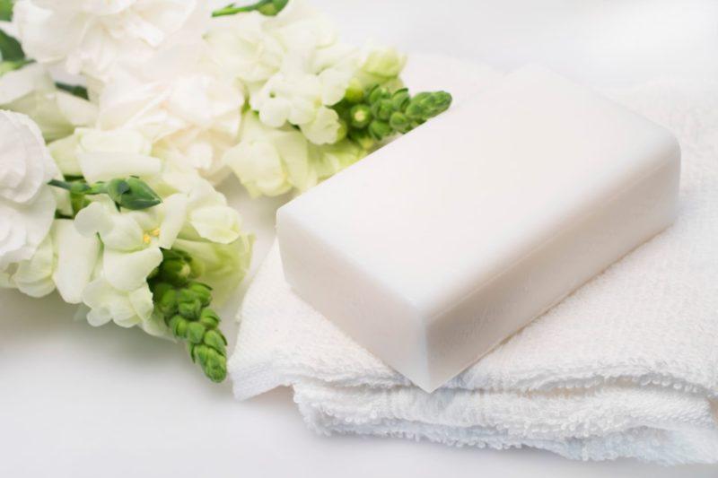 花とタオルの上に置かれた新しい石鹸