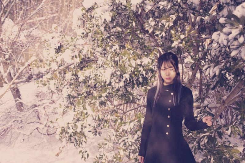 雪が降った後の木のそばに立っている女性