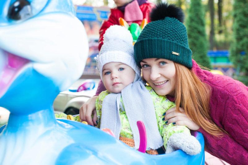 メリーゴーランドに子どもを載せている外国人の親子
