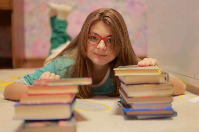 本に触れて寝っ転がっているメガネを掛けた女の子