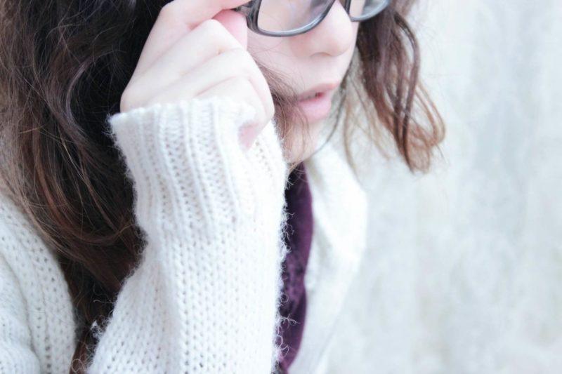 メガネに手を掛けている白いワンピースの女性