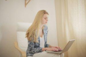 椅子に座ってパソコンを操作している外国人女性