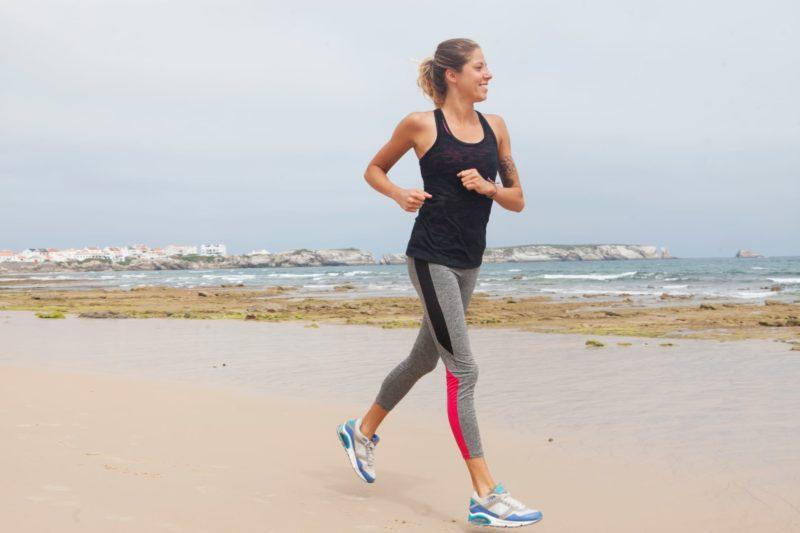 海辺でランニングをしている黒い服の女性