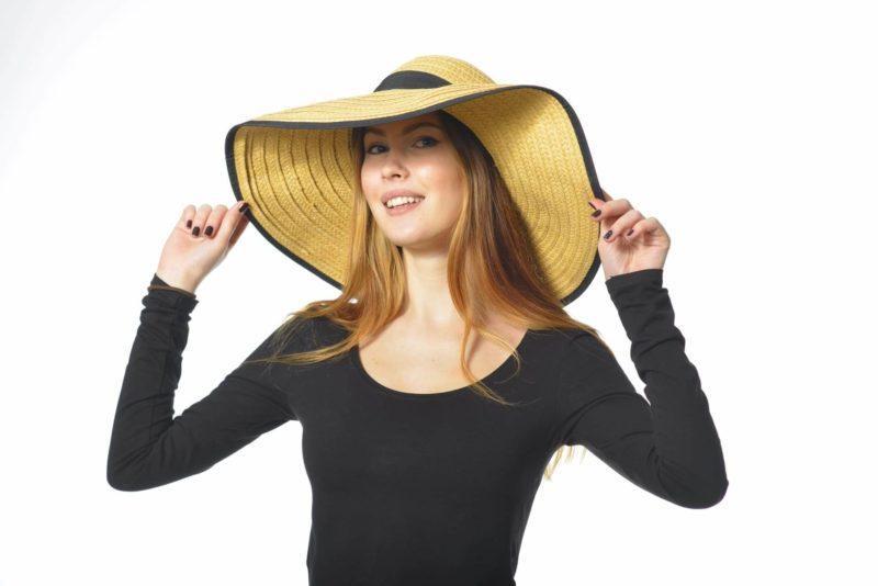 つばの広い麦わら帽子を被った黒い服の外国人女性
