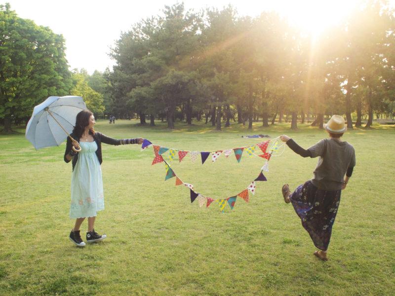 ピクニックに来ている帽子の女性と日傘の女性