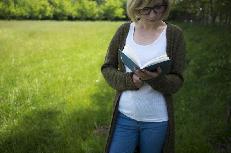 黒のカーディガンを羽織り本を読む女性