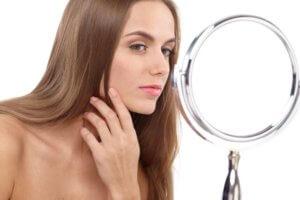 鏡で入念に肌の状態を確かめている女性